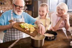 Senioren und Enkelkind backen einen Kuchen