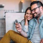 Pärchen mit Handy in der Hand sitzen auf dem Sofa