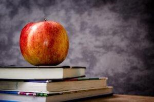 ein roter Apfel liegt auf einem Stapel von 3 Büchern.