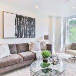 Ein Stilvoll eingerichtetes Wohnzimmer. Ein Sofa, ein Glastisch und moderne Kunst an der Wand.