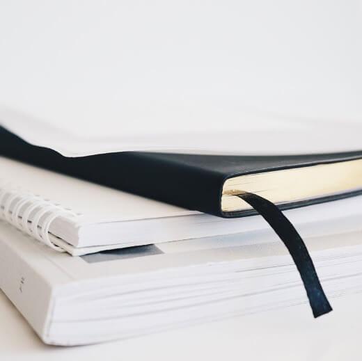 Ein Stapel an Dokumenten, mit einem Buch, einem Ringheft und einem Planer