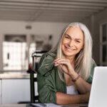 Eine ältere Frau sitzt vor einem Laptop. Sie hält eine Brille in der Hand und lächelt in die Kamera