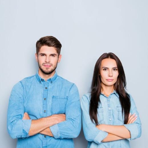 Ein Mann und eine Frau mit verschrenkten Armen. Thema: Immobilie in der Scheidung